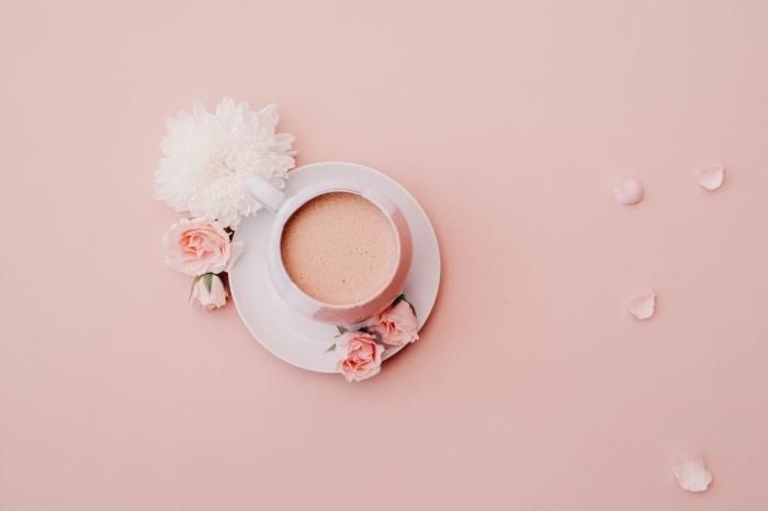 photo rose d'une tasse de café en avant plan, exemple fon decran pour bon début de la journée, prendre une jolie photo à la maison