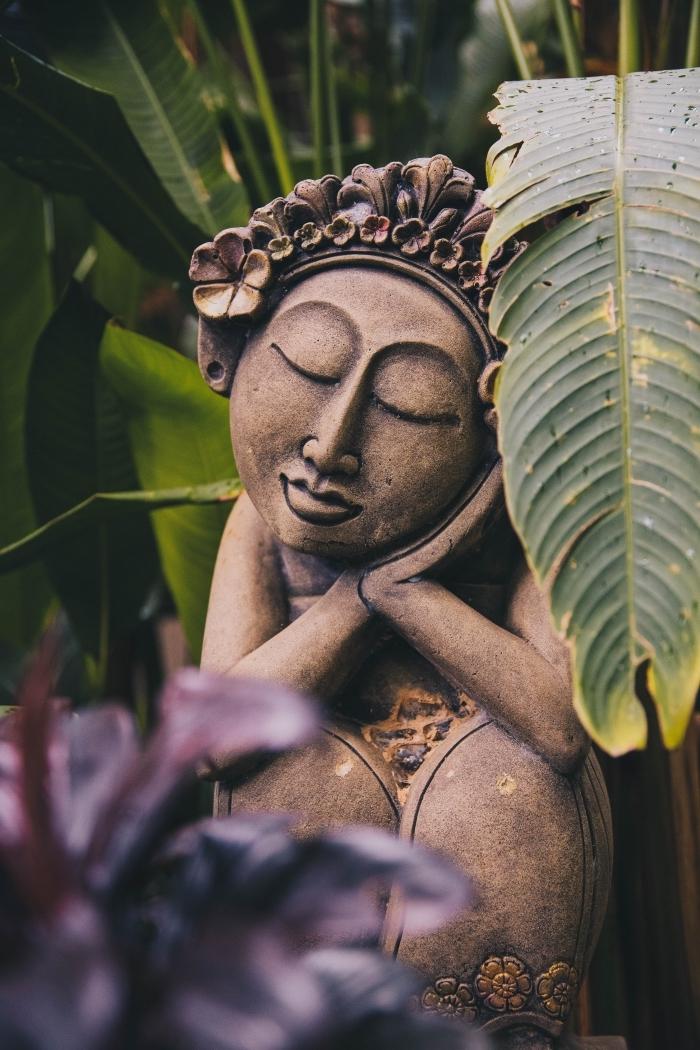 photo d'un jardin zen avec grande statuette bouddha, exemple wallpaper iphone sur le thème zen, idée plantes vertes pour une déco zen dans le jardin