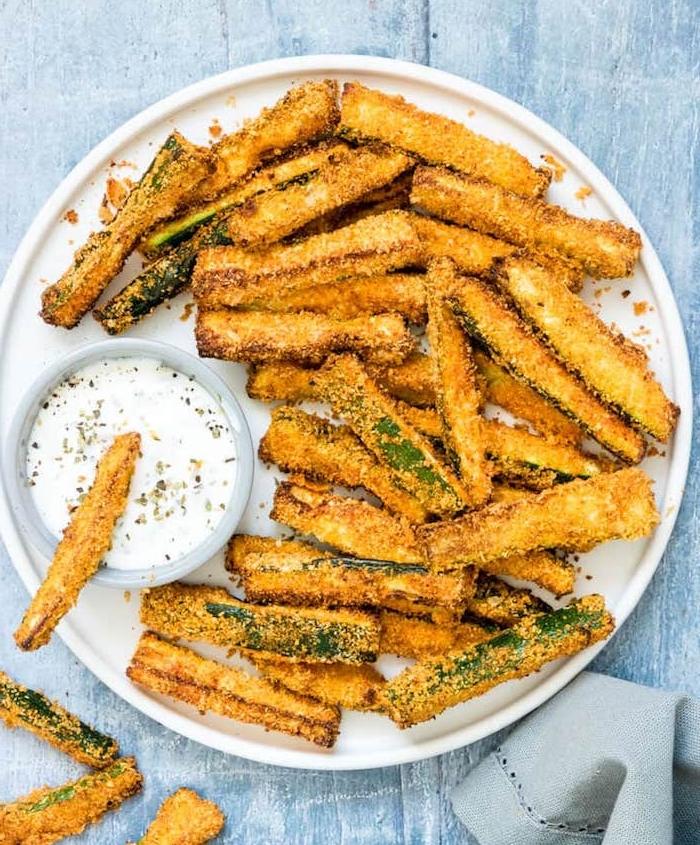comment faire des frites saines de tranches de courgettes au parmesan servies avec de la sauce de yaourt, repas à partager entre amis cetogene