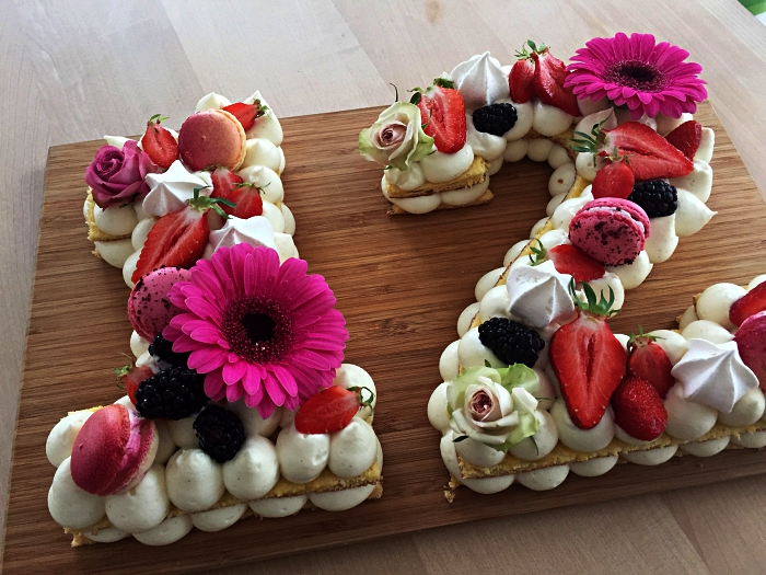 gateau anniversaire facile sur une base de biscuit garni de meringues en buttercreal, macarons et fruits rouges