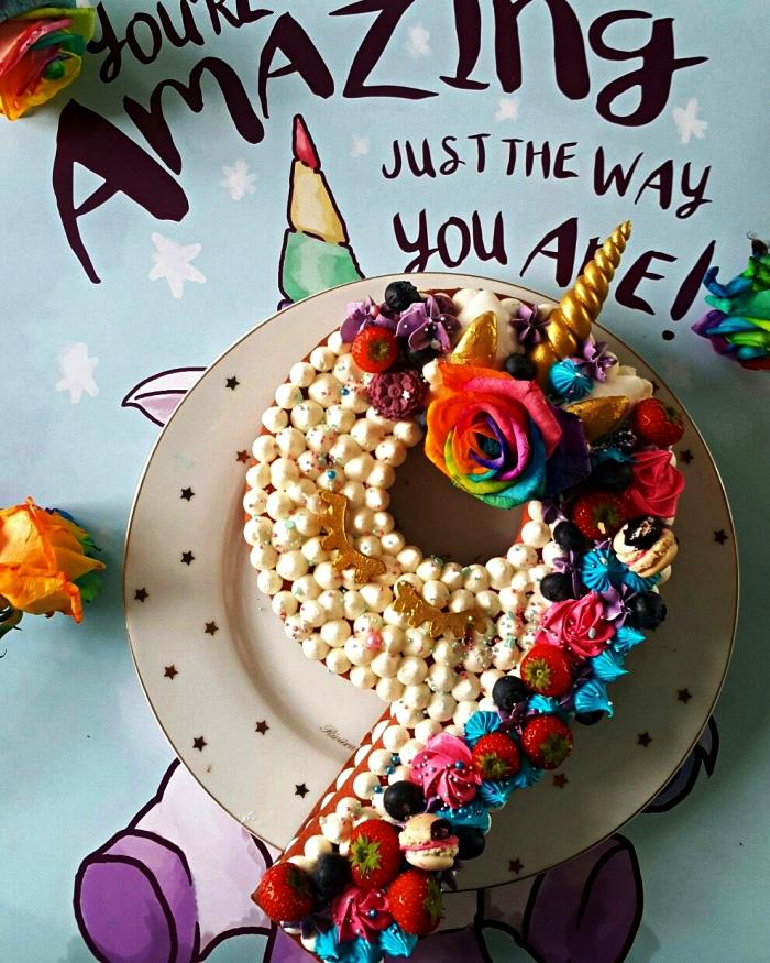 gateau anniversaire enfant sur le thème licorne, gâteau en forme de chiffre garni de meringues en buttercream, fraises et meringues croquantes colorées