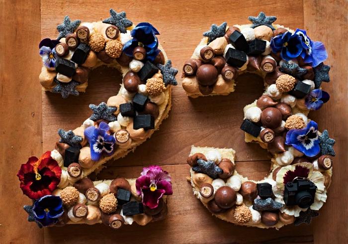 gateau anniversaire adulte en forme de chiffre, gâteau biscuits garni de bonbons pralinés, confiserie, fleurs comestibles et meringues en crème au beurre