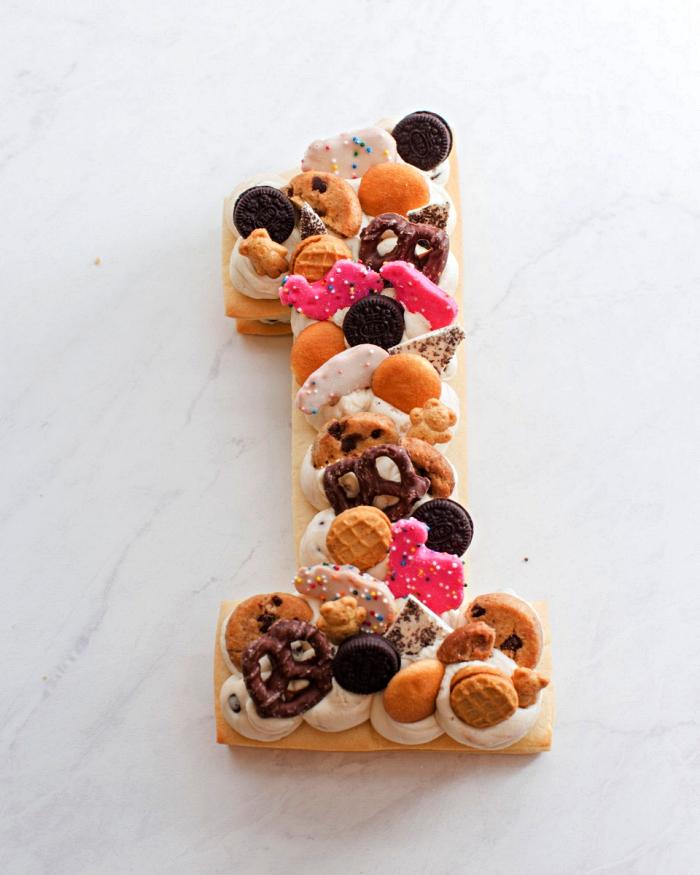 gateau anniversaire 1 an sur une base en pâte sablée au décor de biscuits au chocolat, à la vanille et au glaçage rose