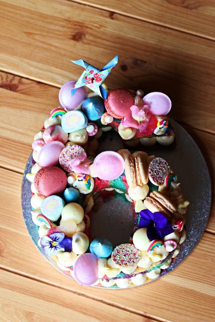 gateau anniversaire enfant en forme de chiffre décoré de toutes sortes de confiseries, de macarons et de crème beurre, idée gâteau anniversaire 6 ans pour fille