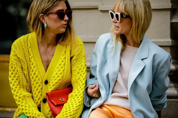 gilet tricoté couleur limonade, petit sac rouge, veste bleue, pull blanc, lunettes de soleil surdimensionnées