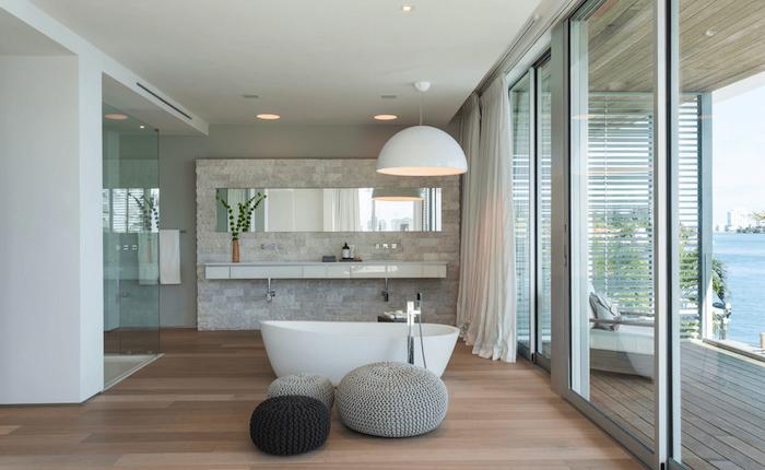 Lustre géant en haut de baignoire oeuf, tabourets sur le sol parquet, vue de la mer, salle de bain blanche et bois, plan de travail salle de bain