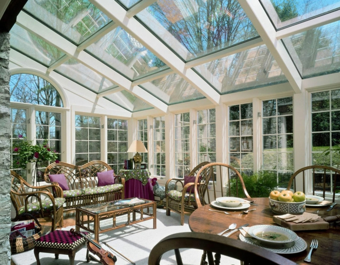 amenagement de veranda mus et toiture vitrée, véranda blanche, meubles en bois foncé, coussins lilas