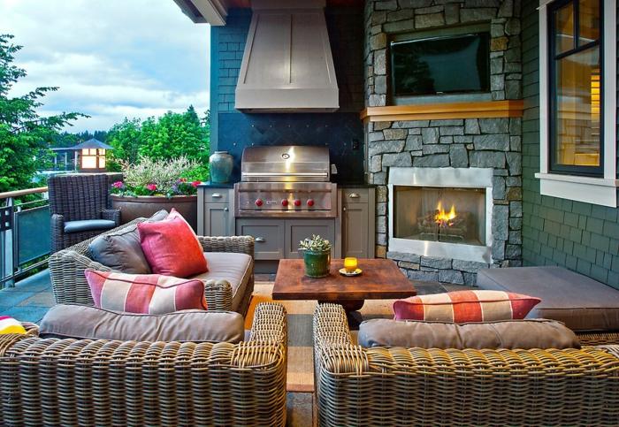 fauteuils en rotin, coussins rayées, table basse en bois, cheminée parement pierre, veranda ouverte