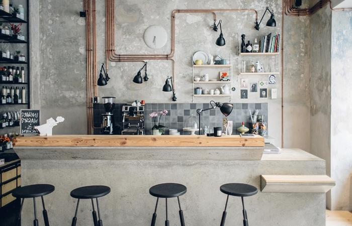 comment décorer une cuisine style industriel aux murs bétons avec tuyaux apparentes et meubles en bois et métal