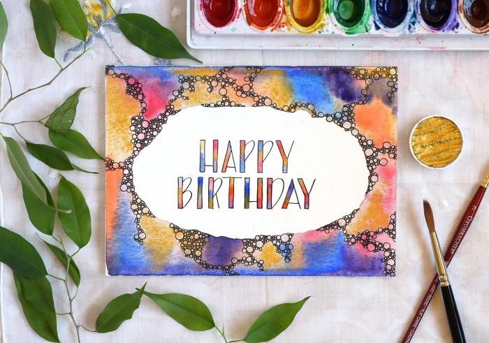 faire une carte d'anniversaire colorée avec une bordure décorée à l'aquarelle, lettrage manuscrit joyeux anniversaire multicolore