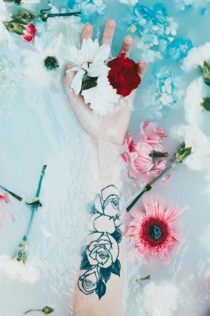 Main dans un baignoire et fleurs dans l'eau tatouage fleur rose, tatouage dessin, la signification de mon tatou