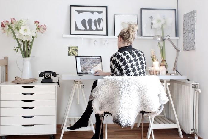 Fille qui travaille sur son ordinateur sur un bureau mouvable, vase de fleurs, rangement chambre, comment ranger sa chambre et la décorer bien