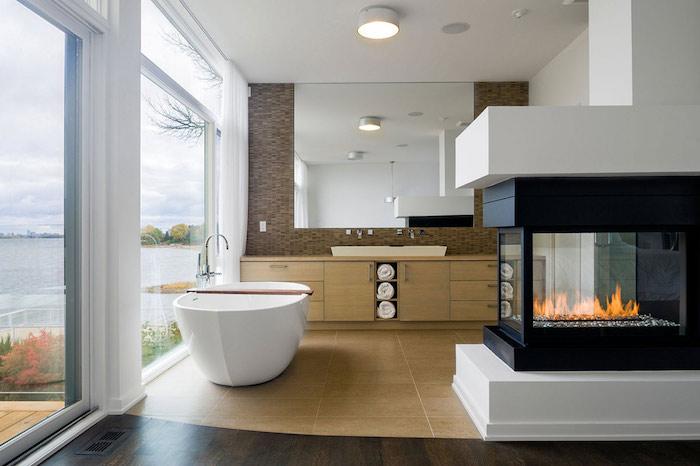 Cheminée dans une belle salle de bain scandinave style luxueuse, espace privé bien décoré, belle bue de la mer, grand miroir
