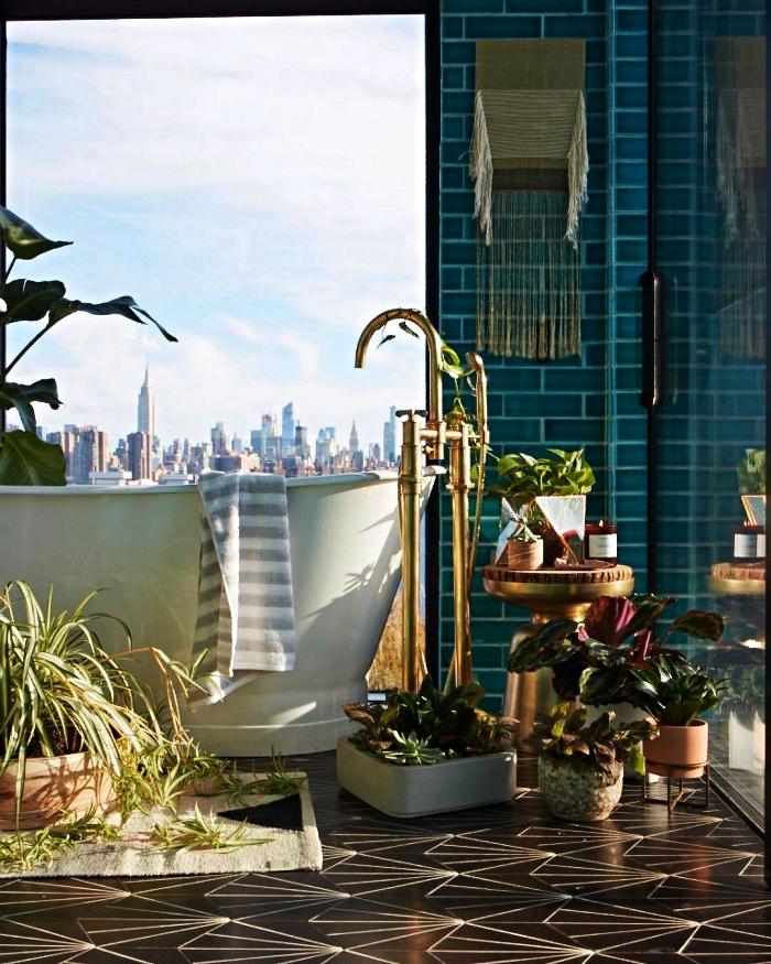 une salle de bain zen et nature en carrelage métro bleu avec espace baignoire relaxant décoré de plantes vertes