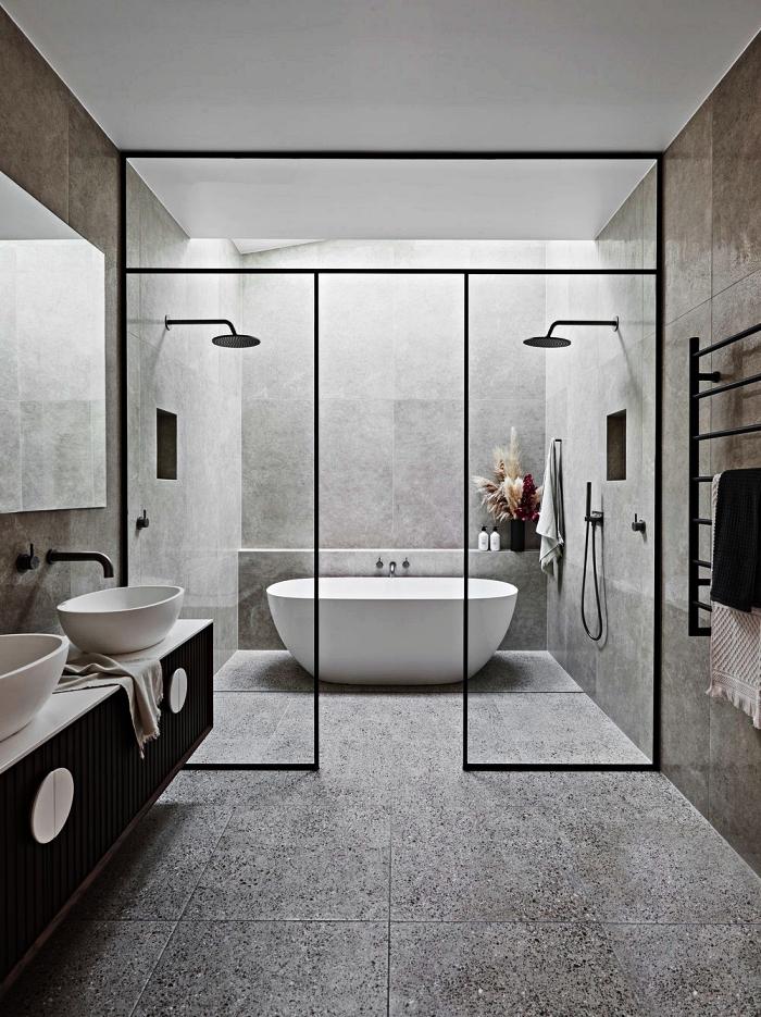 salle de bain contemporaine en carreaux effet ciment avec douches et baignoire îlot délimitées par une verrière