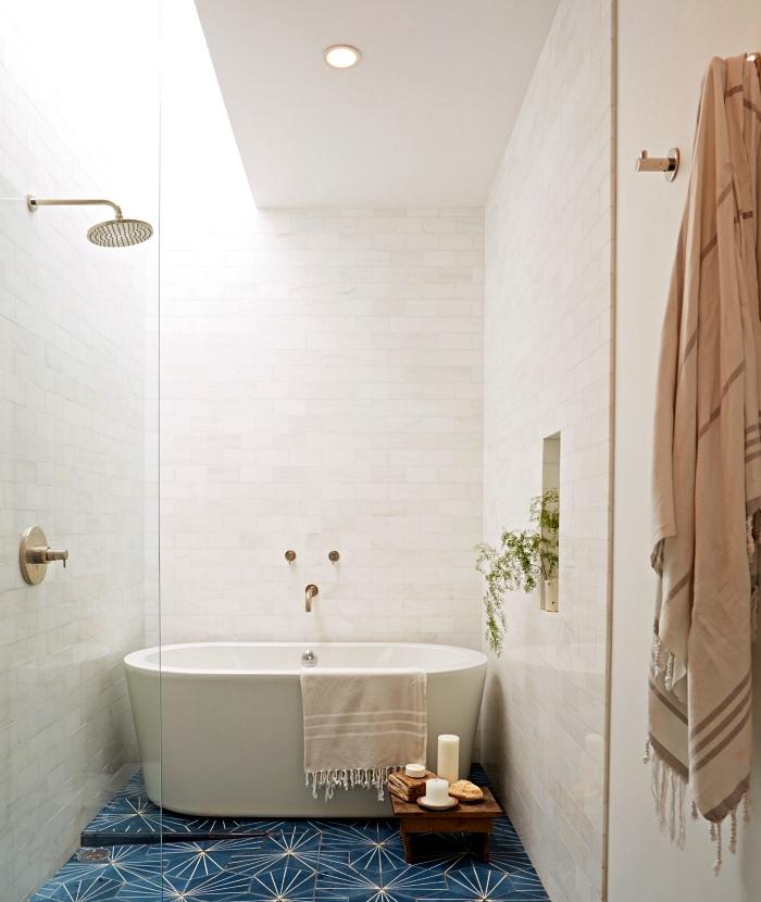 une salle de bain blanche avec douche et baignoire qui semblent se fondre dans le décor