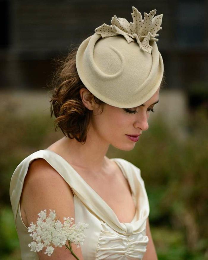 chapeau beige, feuille en tissu décorant le chapeau, carré cheveux bouclés , robe crème
