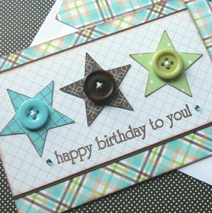 une carte d'anniversaire scrapbooking en papier à motifs carreaux décorée d'étoiles en papier et de boutons