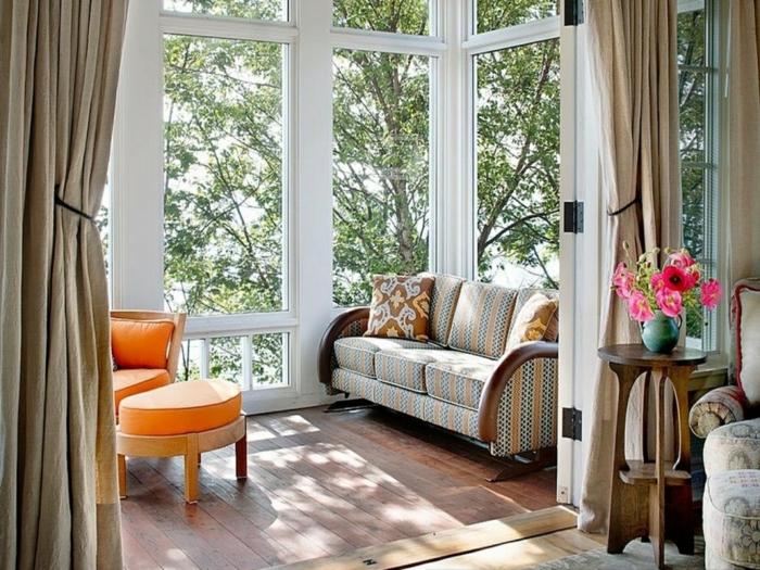 petite veranda sympathique, chaise orange, grandes fenêtres blanches, table haute, vase turquoise