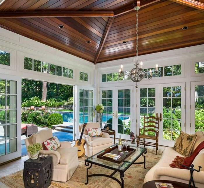 pièce lumineuse, séjour dans véranda, toiture en bois, murs fenêtres, sofas crème, guitare
