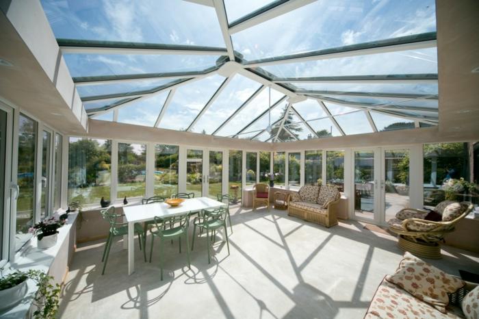 terrasse blanche fermée, table blanche rectangulaire, sofa aux motifs floraux, grande véranda lumineuse