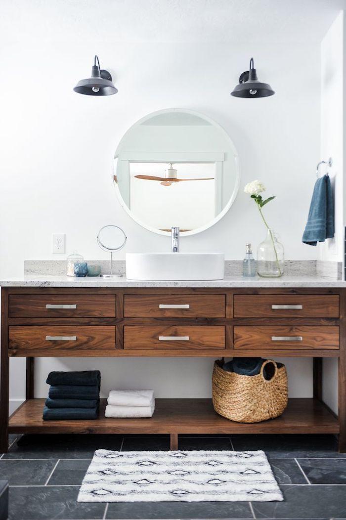 Ronde miroir, grande vase en verre avec une belle fleur blanche, deux lustres style industriel, meuble lavabo avec placards et partie de rangement linge dans basket ou pas