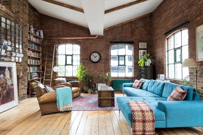 salon spacieux à deco industrielle avec murs en briques et plancher bois, meubles de salon fauteuils en cuir marron