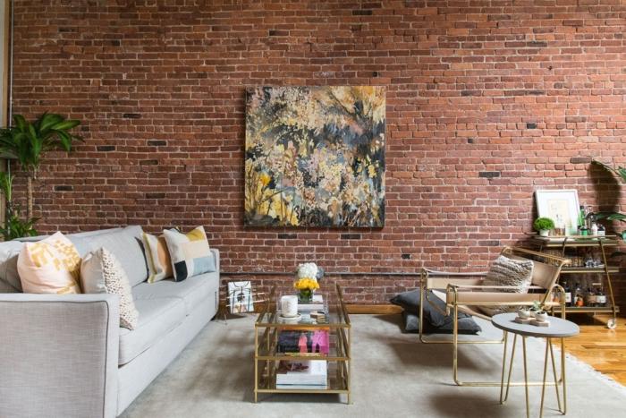 idée chaise style industriel à finition or, déco salon aux murs briques avec canapé blanc et table basse verre et or