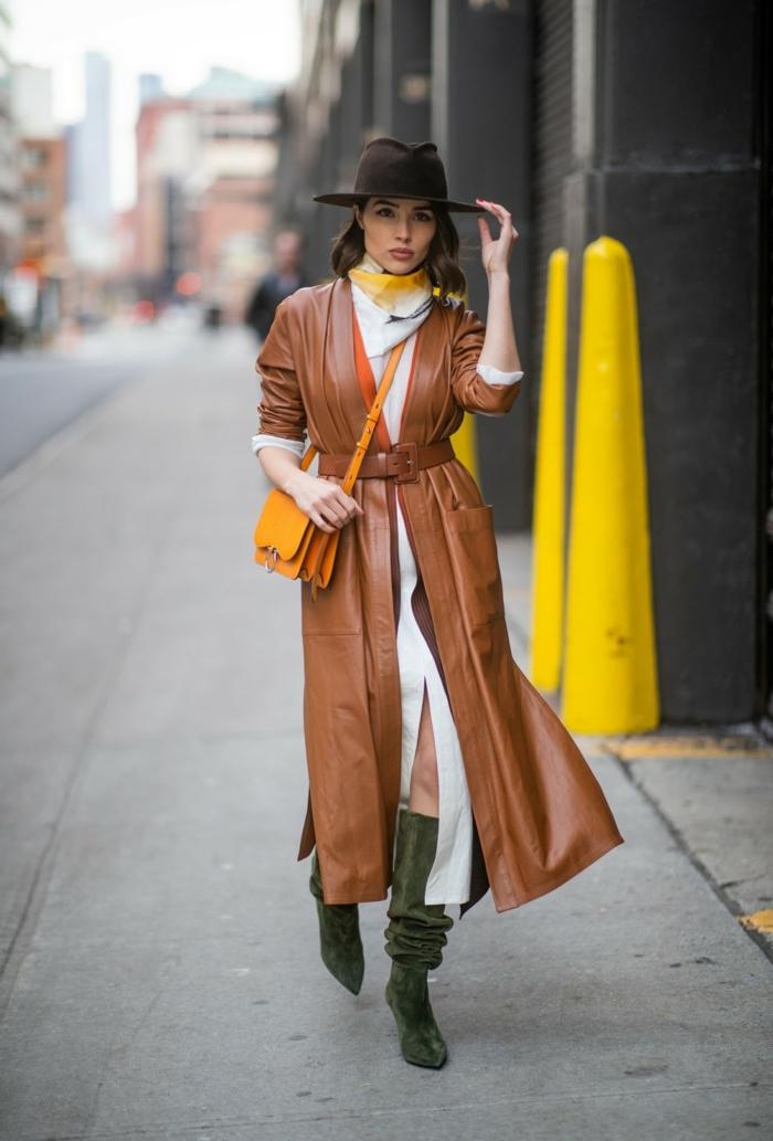 long manteau en cuir, robe blanche longue, bottes en daim, petit sac couleur moutarde, chapeau en feutre