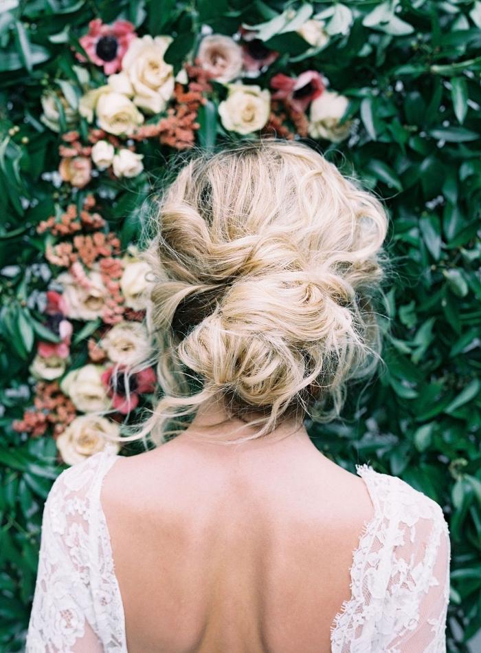 look de mariée bohème chic en robe dentelle à dos nu, chignon mariée bas de style bohème chic sur cheveux longs ondulé, chignon élégant coiffé-décoiffé