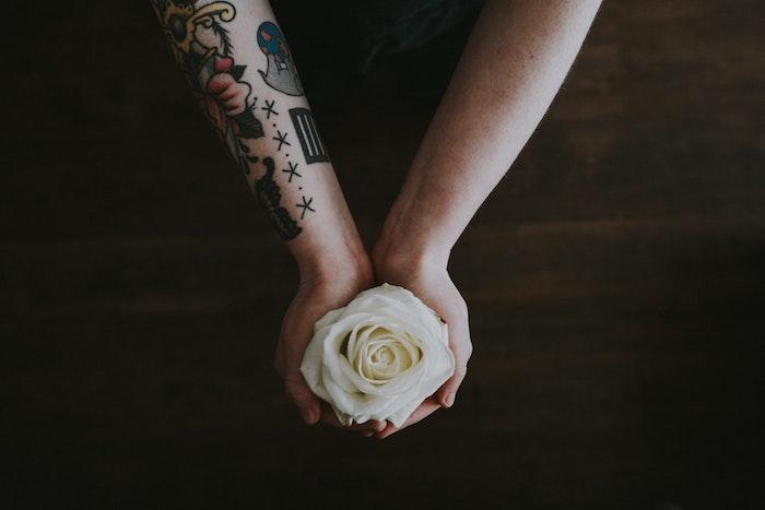 Rose blanche dans les mains, tatouage main style old school, swag tatouage avant bras, le design le plus cool