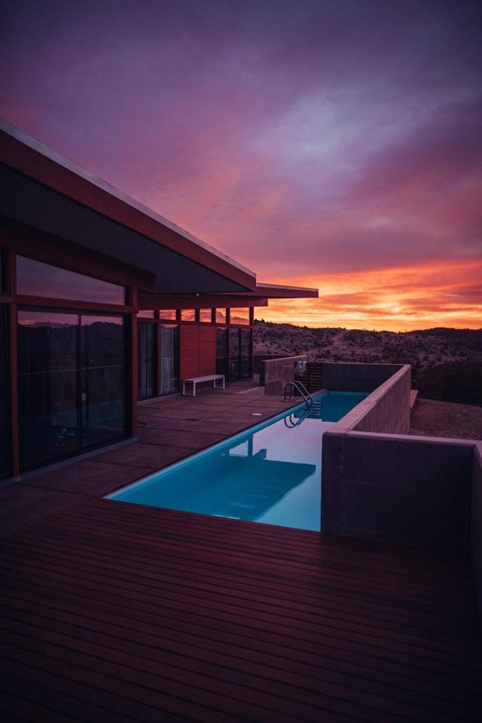une villa moderne avec piscine coque rectangulaire entourée d'une terrasse en bois sous les derniers rayons du soleil couchant