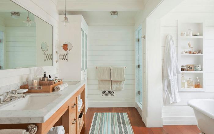 Grand placard, rangement étagère blanche dans le mur, baignoire et douche séparés, tapis de salle de bains bleu, vert et gris et meuble lavabo bois avec nuance rose