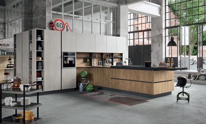 modèle de cuisine industrielle aux murs et plancher béton, meubles de cuisine en bois blanc avec crédence bois