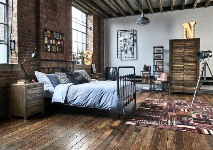 deco industrielle dans une chambre aux murs briques avec plancher bois foncé, modèle de lit industriel en fer forgé