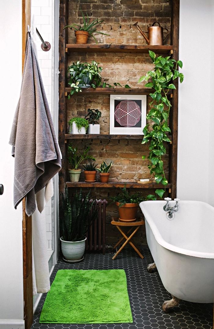 aménagement petite salle de bain avec baignoire sur pieds vintage et une déco de plantes vertes, pan de mur en briques avec des étagères ouvertes aux accents bohèmes chic