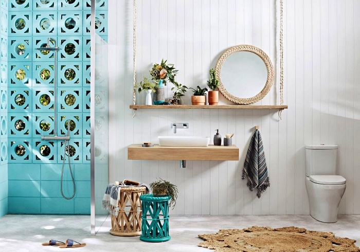 decoration de salle de bain marocaine en blanc et bleu sarcelle, avec douche italienne délimitée par paroi vitrée, plan vasque en bois accordé avec l'étagère suspendue