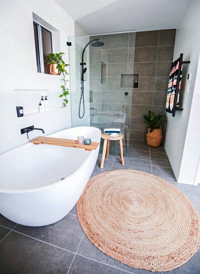 une salle de bain gris et blanc avec une baignoire zen dotée d'un pont de baignoire et une douche italienne délimitée par une paroi discrète en verre