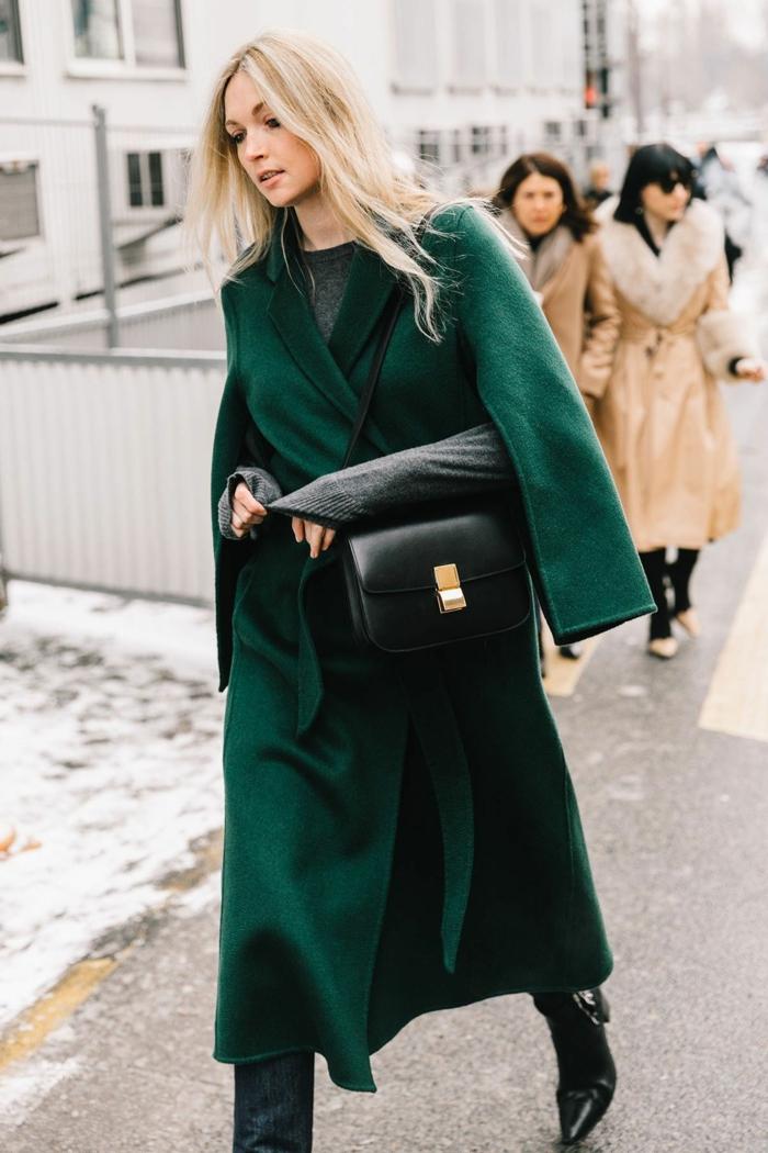 long manteau vert émeraude, sac noir, fermoir doré, cheveux blonds, bottes noires