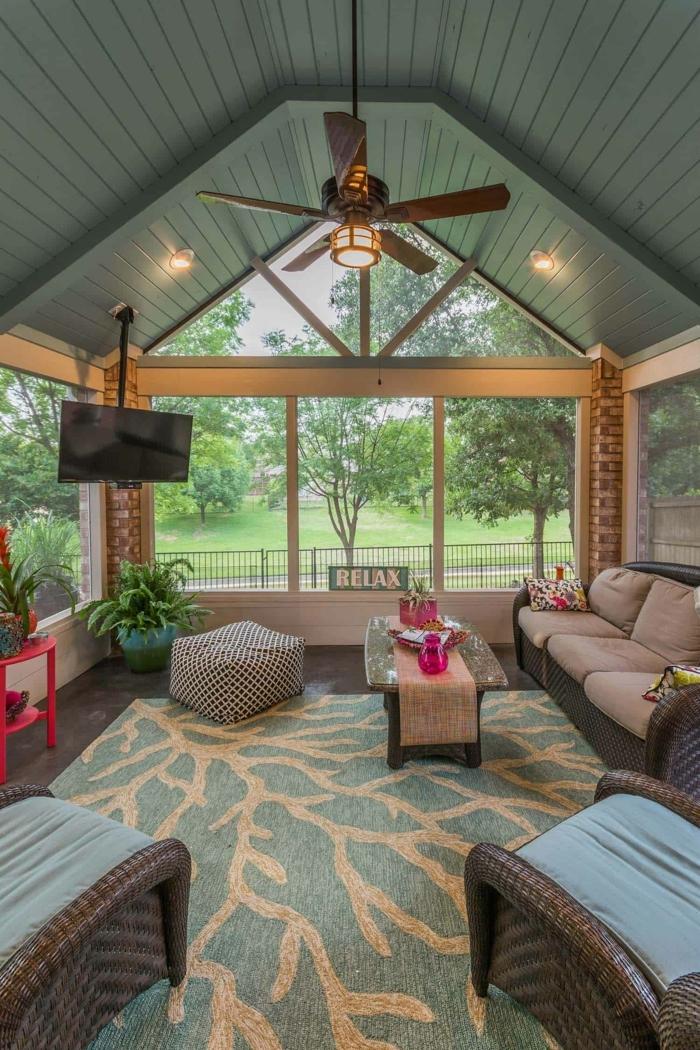 tapis gris et rose, lampe ventilateur, sofa trois places, tv suspendue, table d'appoint rose, décoration de véranda