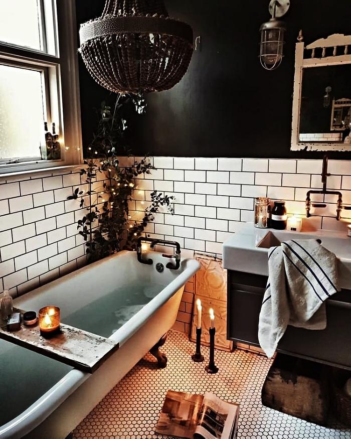 une salle de bain blanche et noire avec baignoire vintage décorée de bougies et de petits objets déco relaxants