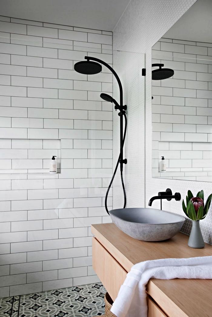 une salle de bain contemporaine au design scandinave épuré avec colonne de douche noir mat et vasque à poser en ciment, des carreaux de ciment au sol pour une touche vintage chic dans la salle de bain