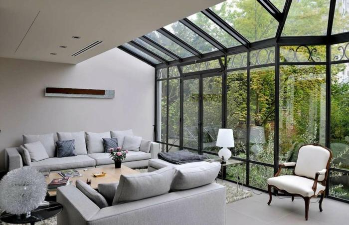 salon gris dans une véranda, sofas gris, fenêtres du plafond au sol, chaise baroque, verrières