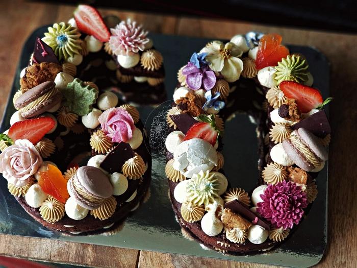 number cake chocolat au décor de meringues, macarons, rosaces en glaçage coloré et morceaux de chocolat