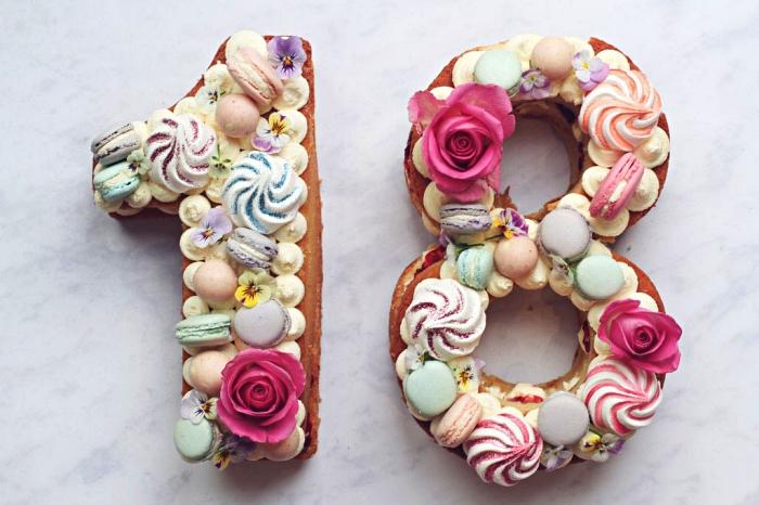 idée gateau 18 ans sur une base de biscuit jaconde garni de crème au beurre vanille, macarons en tons pastel et fleurs comestibles