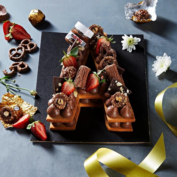 gateau anniversaire chocolat en forme de lettre, gâteau à base biscuits garni de meringues en buttercream chocolat, de ferrero rocher et de fraises, gâteau au nutelle en forme de lettre