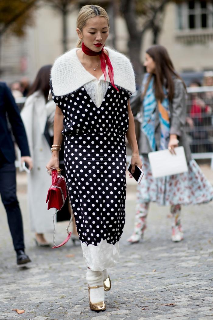 robe noire pointillée, col blanc moelleux, ruban rouge autour du cou, petit sac rouge, chaussures dorées