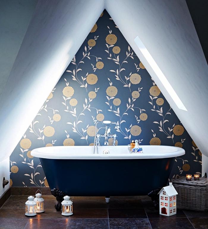 amenagement petite salle de bain sous les combles, coin relaxant aménagé sous pente avec baignoire bleu marine et un pan de mur en papier peint imprimé floral