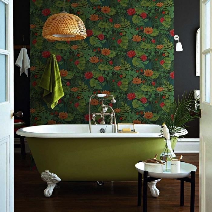 une salle de bain nature d'ambiance relaxante avec une baignoire vintage verte mise en avant par un pan de mur en papier peint tropical, ambiance intime dans une salle de bains aux tons foncés et aux accents végétaux