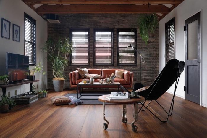 modèle de canapé style industriel en cuir marron, revêtement mural en briques, plantes vertes d'intérieur style bohème